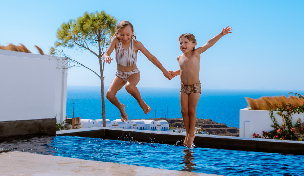 Children jumping in pool at Andronis Arcadia, Oia, Santorini, Greece